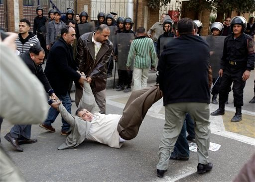 Egyptian plain cloth policemen arrest Mohamed Abdul Quddus, Rapporteur of the civil Liberties Committee and member of the Press Syndicate Council, outside the journalists syndicate in downtown Cairo, Egypt, Jan. 26, 2011. (AP Photo/Ben Curtis)