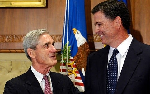 Former FBI Director James Comey talks with outgoing FBI Director Robert Mueller before Comey was officially sworn in at the Justice Department in Washington.