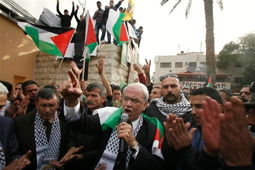 Senior Palestinian negotiator Saeb Erekat, center, surrounded by Fatah supporters speaks during a rally in the West Bank town of Jericho, Tuesday, Jan. 25, 2011.