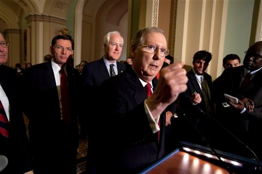 Sens. John Barrasso, R-Wyo., and John Cornyn, R-Texas, listen as Senate Minority Leader Mitch McConnell speaks to reporters after the weekly caucus luncheons in Washington in this Jan. 25, 2011, file photo. (AP Photo/Harry Hamburg, file)