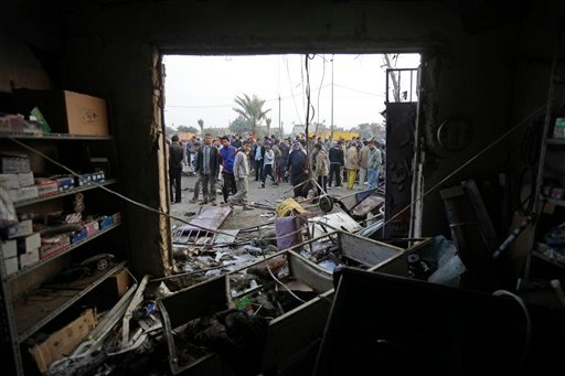 People gather around a destroyed shop at the scene of a car bomb attack in Baghdad, Iraq Jan. 27, 2011. (AP Photo/Khalid Mohammed)