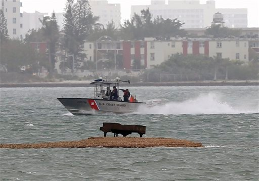 A U.S. Coast Guard boat passes near a grand piano on a sandbar in Biscayne Bay, Jan. 25, 2011 in Miami. The piano recently showed up on the sandbar, about 200 yards from condominiums on the shore. (AP Photo/Wilfredo Lee)