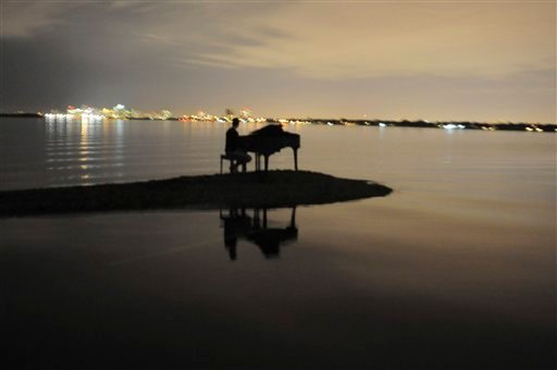 In this Jan. 2, 2011 photo provided by Nicholas Harrington, Julian Kolevris-Roots, 18, is shown sitting at a piano on a sandbar in Miami's Biscayne Bay. (AP Photo/Nicholas Harrington)