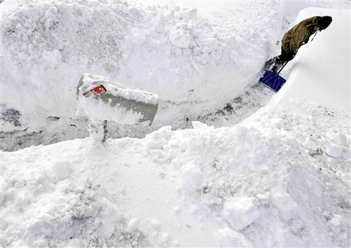 A man shovels a walkway to a mailbox in Manchester, Conn., after a winter snow storm, Thursday, Jan. 27, 2011. (AP Photo/Jessica Hill)