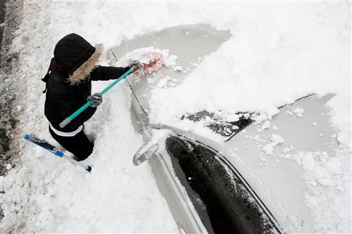 Evelyn Santana, 28, of Newark, N.J., cleans snow off her vehicle, Thursday, Jan. 27, 2011, in Newark. (AP Photo/Julio Cortez)