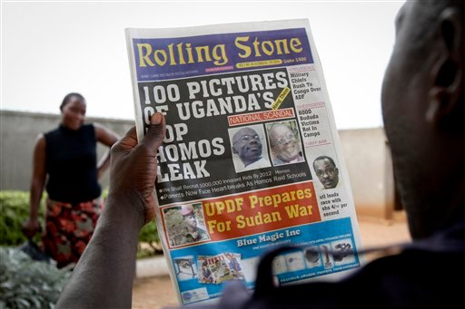 """In this Tuesday Oct 19 2010 photo, a man reads the headline of the Ugandan newspaper """"Rolling Stone"""" in Kampala, Uganda, in which the paper reveals the identity of allegedly gay members of Ugandan society and calls for public punishment."""