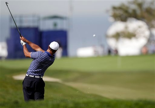 Tiger Woods hits from the rough toward the 12th green during a pro-am for the Farmers Insurance Open golf tournament in San Diego, Wednesday, Jan. 26, 2011.