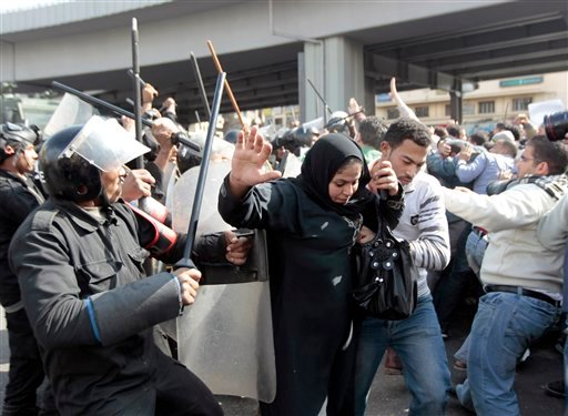An Egyptian woman flees as Egyptian anti-riot policemen clash with protesters in Cairo, Egypt, Friday, Jan. 28, 2011.