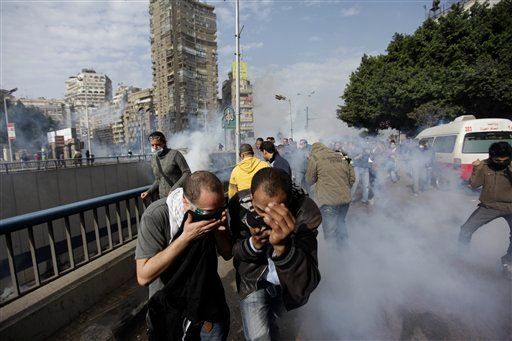 Egyptian anti-government activists run for a cover from the tear gaz during clashes with the riot- police in Cairo, Egypt, Friday, Jan. 28, 2011.