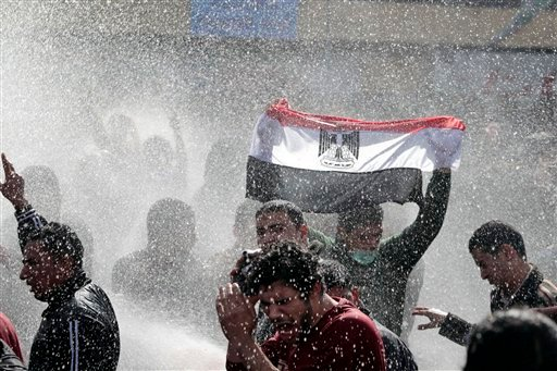 An Egyptian protester flashes Egypt's flag as anti-riot policemen use water canon against protesters in Cairo, Egypt, Friday, Jan. 28, 2011.