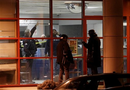 Detroit police officers look over the scene in and outside the precinct 6 building in northwest Detroit where a gunman walked into the police station and opened fire injuring three police officers, Sunday, Jan. 23, 2011.