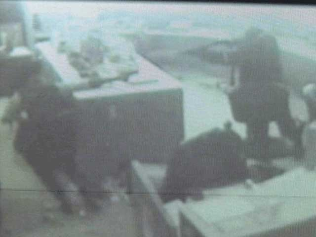 Video capture showing Lamar Moore walking into the precinct and firing shots at police officers.