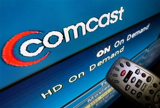 In this Aug. 6, 2009 file photo, the Comcast logo is displayed on a TV set in North Andover, Mass. Comcast, the nation's largest cable TV company, says it will complete its takeover of NBC Universal. (AP Photo/Elise Amendola, File)