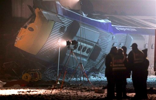 Rescue workers stands beside bodies of casualties after a train crash in Hordorf near Oschersleben, eastern Germany, Sunday morning, Jan 30, 2011. (AP Photo/dapd, Ronny Hartmann)