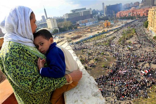 An Egyptian mother hugs her child as she watches some thousands of Egyptian protesters gather at Tahrir square in Cairo, Egypt, Sunday, Jan. 30, 2011. (AP)