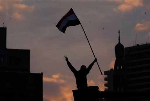 A protester waves an Egyptian flag after he climbed on a lampost during a demonstration in Tahrir square in downtown Cairo, Egypt, at dusk, Sunday, Jan. 30, 2011. (AP Photo/Khalil Hamra)