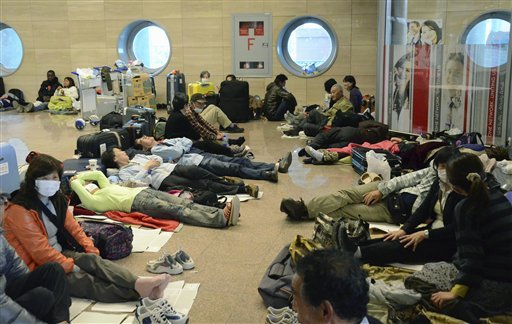 Japanese tourists take rest in the lobby of the Cairo airport as their homebound flights were canceled Sunday, Jan. 30, 2011. (AP Photo/Kyodo News, Takeshi Tsuchiya)
