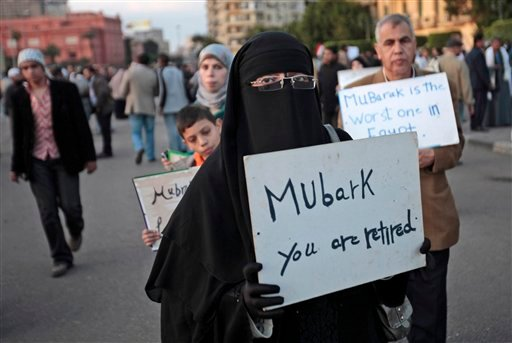 A woman carrying a placard referring to Egyptian President Hosni Mubarak attends a demonstration by anti-government protesters in Cairo's Tahrir Square, Egypt, Monday, Jan. 31, 2011.