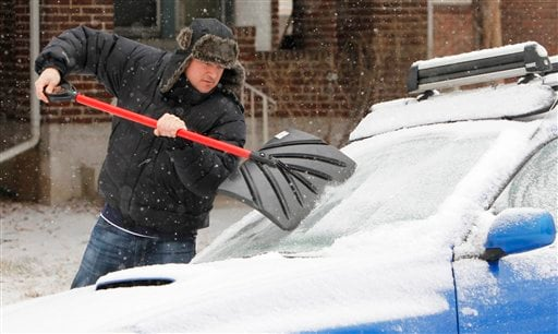 Tom Gillian uses a snow shovel to scrape ice from the windshield of his car in Denver Monday, Jan. 31, 2011. A front moved through the state early Monday morning bringing with it freezing rain, snow and cold.