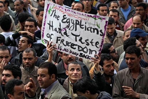 "An anti-government protester holds a banner reading ""The Egyptians had a taste of freedom. There is no way back"" during the continuing demonstration in Tahrir Square in downtown Cairo, Egypt, Tuesday, Feb. 1, 2011."