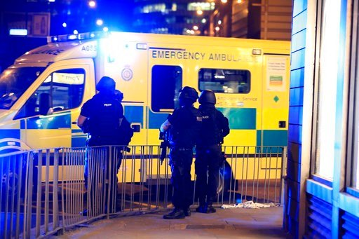 Armed police stand next to an ambulance after an explosion at the Manchester Arena in Manchester, England Tuesday, May 23, 2017. ( Peter Byrne/PA via AP)