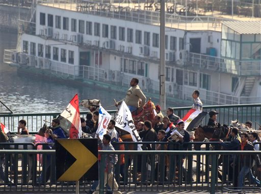 Supporters of President Hosni Mubarak cross a bridge over the river Nile as they march towards anti-Mubarak protesters in Cairo, Egypt Feb. 2, 2011. (AP Photo/Amr Nabil)