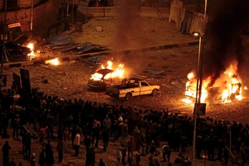 Pro-government demonstrators, bottom, watch as cars burn during clashes with anti-government demonstrators, not seen, in Tahrir square, the center of anti-government demonstrations, in Cairo, Egypt, early Thursday, Feb. 3, 2011.