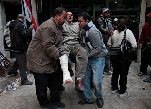 Anti-government demonstrators carry a man wounded during clashes with pro-government protesters, at a makeshift medical triage station, near Tahrir square, the center of anti-government demonstrations, in Cairo, Egypt, Wednesday, Feb. 2, 2011.