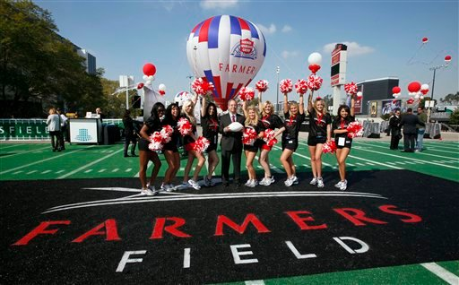 Paul Palsu, Farmers Insurance president, center, poses with Los Angeles Kings cheerleaders, Tuesday, Feb. 1, 2011, during a ceremony naming a new NFL stadium in Los Angeles.