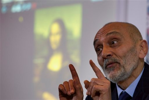 """Art historian Silvano Vinceti gestures as a photo of Italian artist Leonardo da Vinci's """"Mona Lisa"""" painting is projected in background, during a press conference, in Rome, Wednesday, Feb. 2, 2011."""