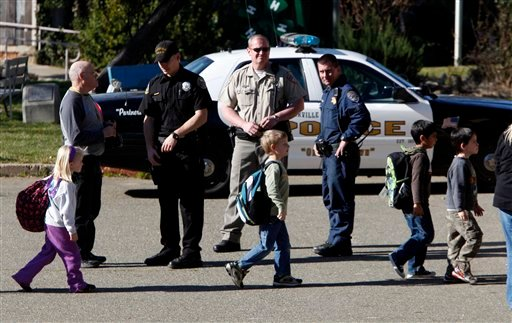Students from the Louisiana Schnell School walk past law enforcement officers after being transported to a nearby fairgrounds following a shooting at the school in Placerville, Calif., Wednesday, Feb. 2, 2011.