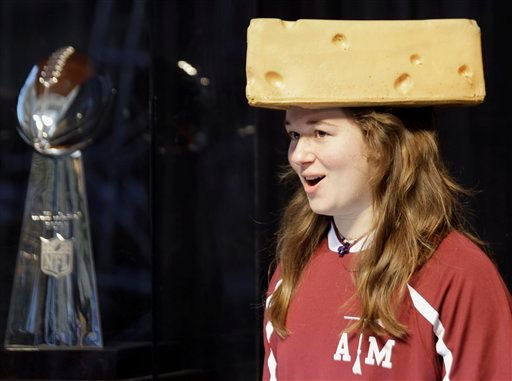 Danielle Kutz, 18, of Corsicana, Texas, wears a Green Bay Packers cheesehead as she poses with the Vince Lombardi Trophy at the NFL Experience Saturday, Jan. 29, 2011 in Dallas.