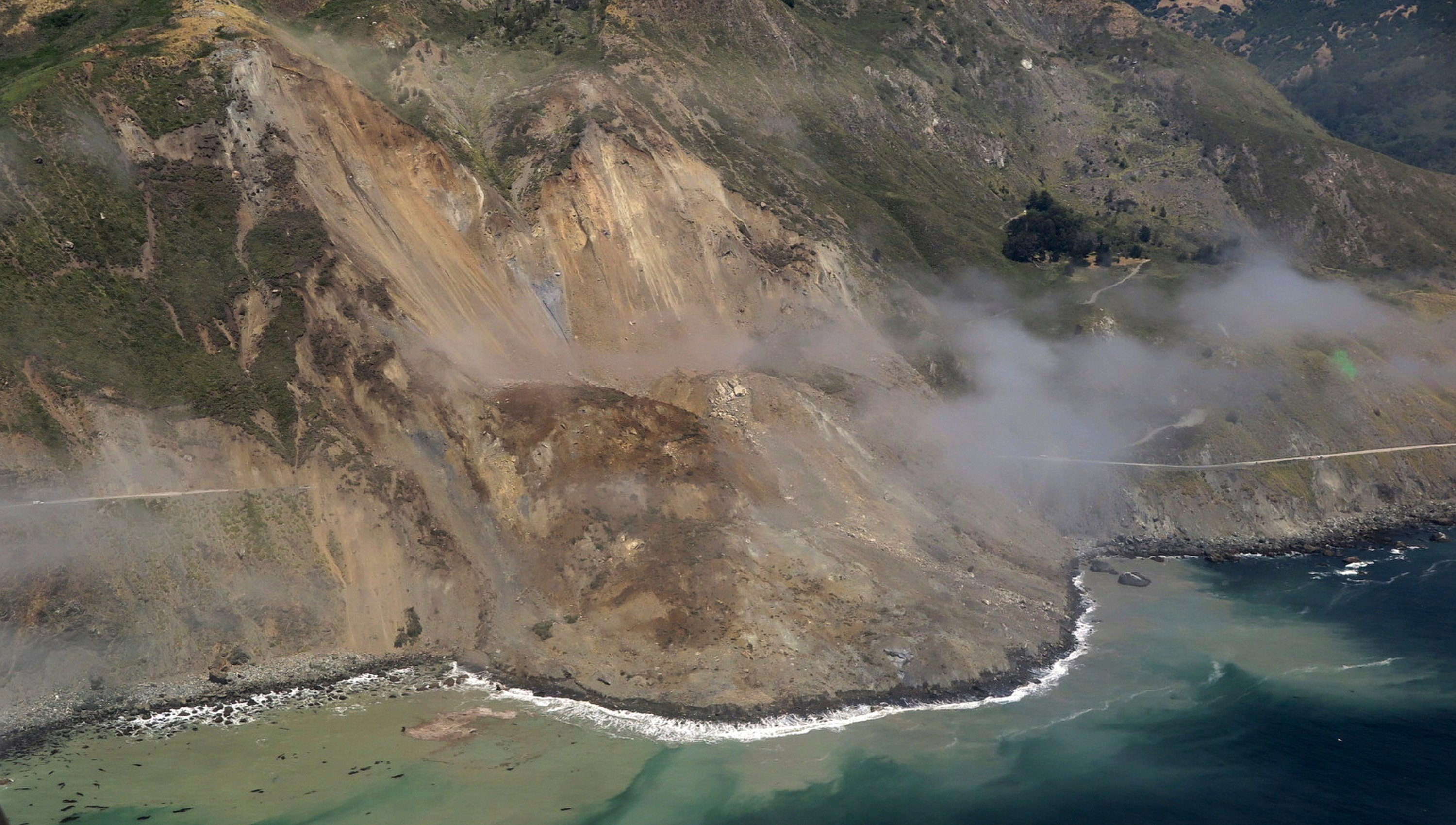 A swath of the hillside gave way in an area called Mud Creek on Saturday, May 20, covering about one-third of a mile, half a kilometer, of road and changing the Big Sur coastline. (John Madonna via AP)
