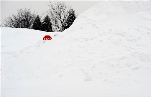 A stop sign pokes out of a large pile of snow at the end of a street in Enfield, Conn., Tuesday, Feb. 1, 2011. (AP Photo/Jessica Hill)