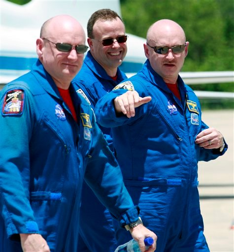 In this May 28, 2008 file photo, Space shuttle Discovery commander Mark Kelly, husband of Rep. Gabrielle Giffords, right, gestures as he walks with his twin brother astronaut Scott Kelly, left, and mission specialist Ron Garan.
