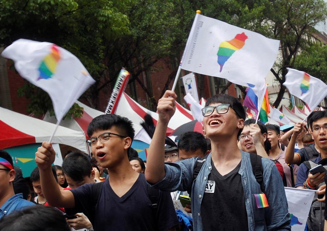 Same-sex marriage supporters wave rainbow Taiwan flags after the Constitutional Court ruled in favor of same-sex marriage outside the Legislative Yuan in Taipei, Taiwan, Wednesday, May 24, 2017. (AP Photo/Chiang Ying-ying)