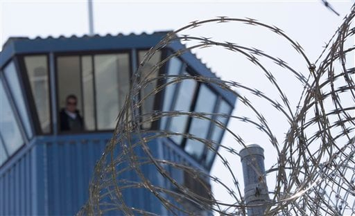 FILE - In this Aug. 17, 2011 file photo, concertina wire and a guard tower are seen at Pelican Bay State Prison near Crescent City, Calif. (AP Photo/Rich Pedroncelli, File)