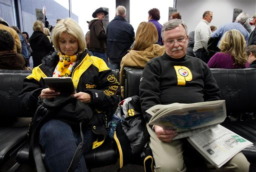 Pittsburgh Steelers fans and Super Bowl XLV ticket-holders Linda Thompson, left, and her husband Brad read at a gate in Louis Armstrong International Airport in Kenner, La., Friday, Feb. 4, 2011, while waiting for an update on their delayed flight.