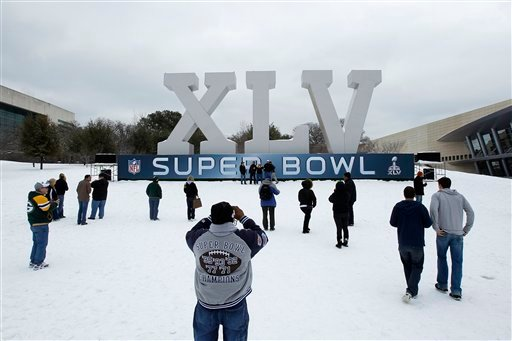 Fans pose for photographs near the NFL Super Bowl Experience during a winter storm, Friday, Feb. 4, 2011, in Dallas. The Green Bay Packers face the Pittsburgh Steelers in NFL football's Super Bowl XLV on Sunday, in Arlington, Texas.