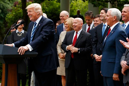 President Donald Trump, accompanied by GOP House members, speaks after the House pushed through a health care bill, in the Rose Garden of the White House, Thursday, May 4, 2017, in Washington. (AP Photo/Evan Vucci)