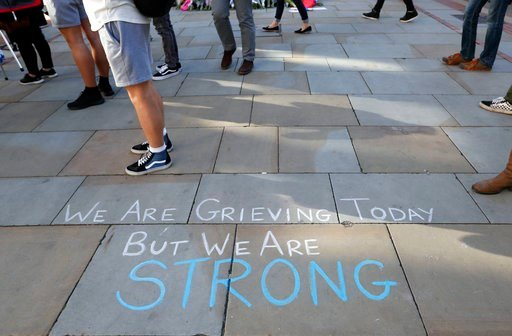 A message is written on the pavement in Manchester, England, Tuesday May 23, 2017, the day after the suicide attack at an Ariana Grande concert that left 22 people dead as it ended on Monday night. (AP Photo/Kirsty Wigglesworth)