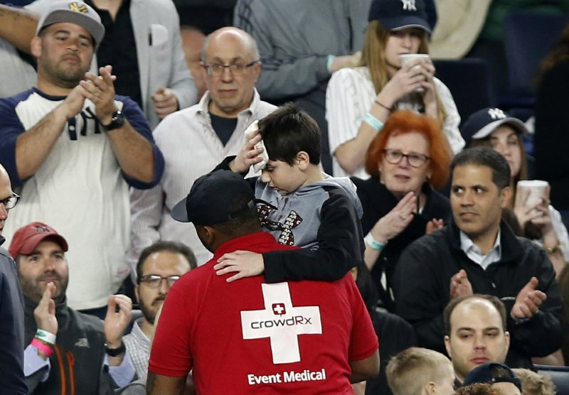 Fans applaud as a medical employee carries an injured youngster from the stands after the boy was hit in the head by a piece the Yankees's Chris Carter's bat that split during the seventh inning of a baseball game against the Kansas City Royals.