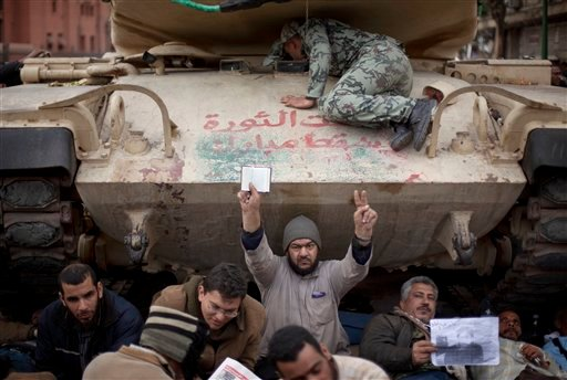 Egyptian anti-Mubarak protesters, one of them holding a copy of the Quran or Muslim holy book, in front of a tank at Tahrir Square in Cairo, Egypt, Sunday, Feb. 6, 2011. (AP)