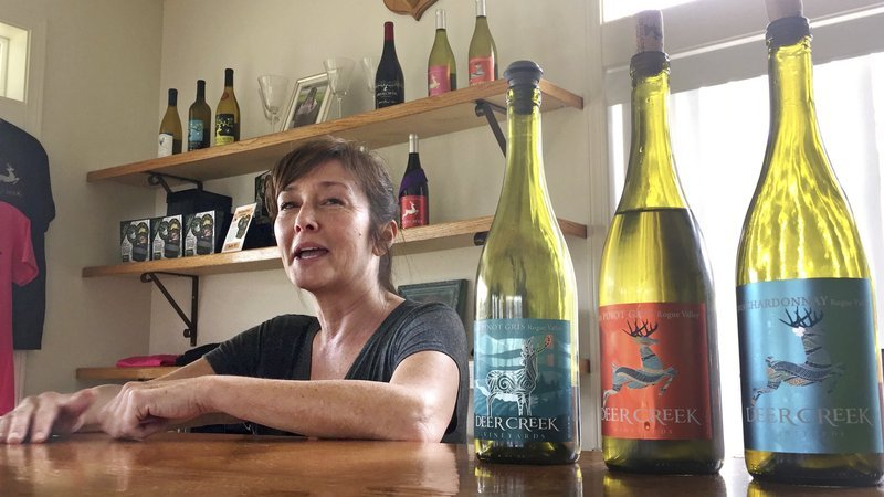 In this April 5, 2017 photo, vineyard owner Katherine Bryan laughs as she discusses the wines available for tasting at Deer Creek Vineyards in Selma, Ore.