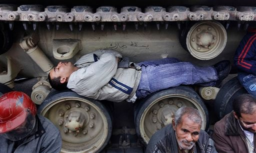Anti-government protesters sit and lie inside the tracks of an Egyptian Army tank, both to prevent them from moving and to shield themselves from the rain. (AP Photo/Ben Curtis)