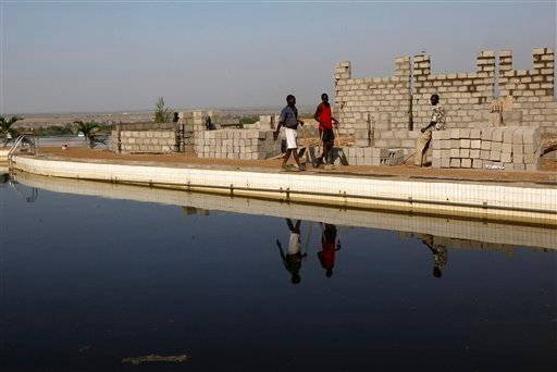 South Sudanese construction workers walk along the country's largest swimming pool Jan. 12, 2011, in Rock City, a 160 apartments and hotel rooms complex under construction in Juba, South Sudan. (AP Photo/Jerome Delay)