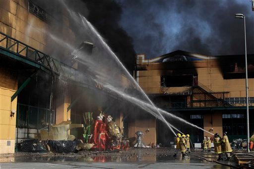 Firefighters try to extinguish a fire at the City of Samba in Rio de Janeiro, Brazil, Monday, Feb. 7, 2011. (AP Photo/Felipe Dana)