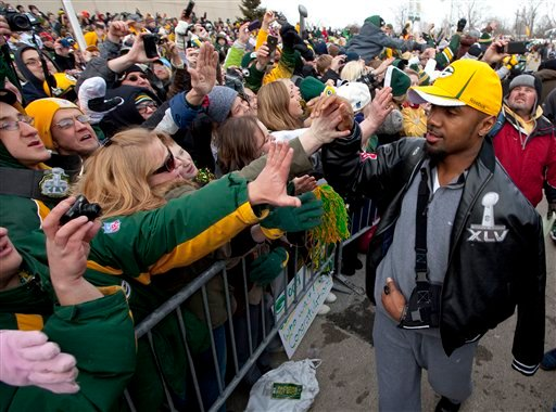 Green Bay Packers cornerback Charles Woodson high-fives fans as the NFL football team returns.