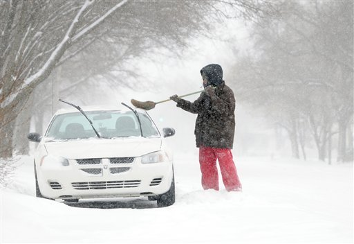 """Marques Lewis sweeps snow from his car, Tuesday, Feb. 8, 2011, in Salina, Kan. Lewis said he was """"getting ready to go to work"""" and had to """"start a little early."""" (AP Photo/Salina Journal, Tom Dorsey)"""