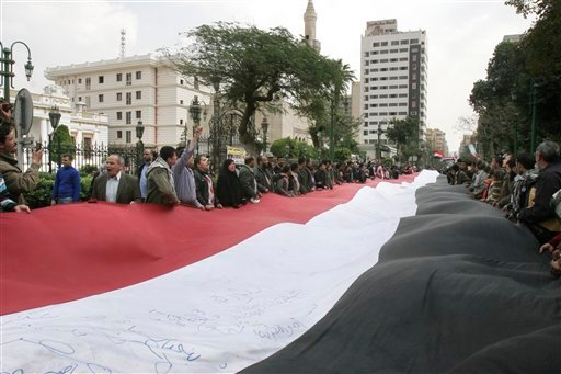 Egyptian protesters wave a giant flag in front of the Egyptian Parliament in Cairo, Egypt, Wednesday, Feb. 9, 2011. (AP Photo/ Mohammed Abou Zaid)